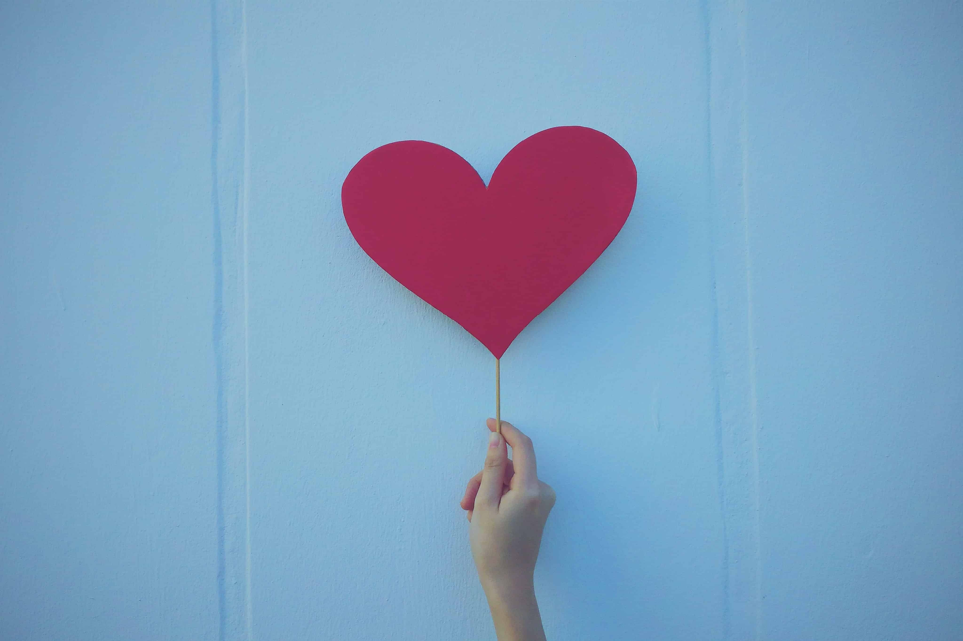 An image of a hand holding a paper heart