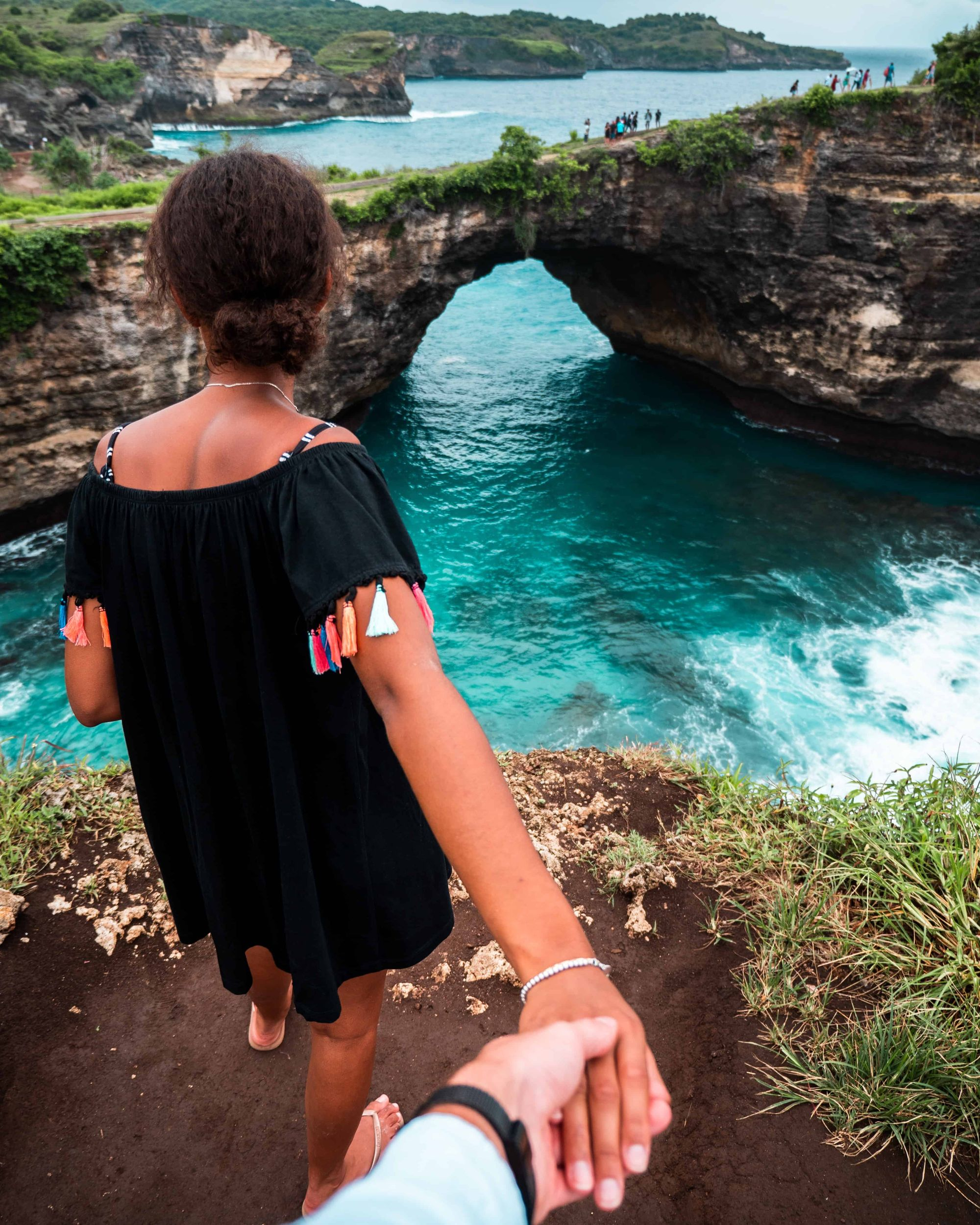 Photo of a woman looking at the ocean holding a man's hand
